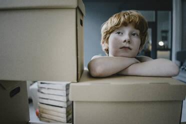 Portrait of redheaded boy leaning on cardboard box - KNSF06273