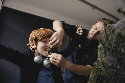 Father decorating his son at Christmas time - KNSF06276