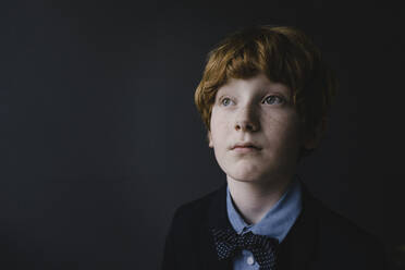 Portrait of redheaded boy with freckles wearing bow tie looking up - KNSF06279
