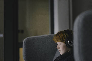 Profile of redheaded boy with headphones on wingback chair - KNSF06285