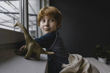 Portrait of redheaded boy leaning on window sill in the evening - KNSF06288