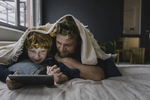 Father and son lying together under blanket looking at digital tablet - KNSF06291