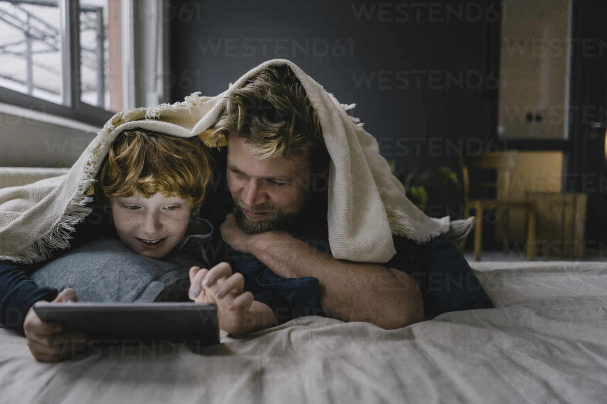 Father and son lying together under blanket looking at digital tablet - KNSF06291 - Kniel Synnatzschke/Westend61