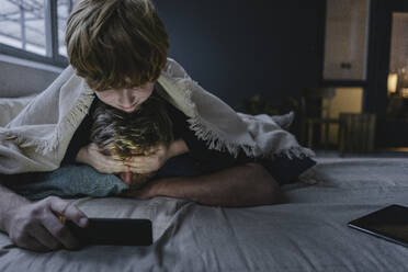 Father and son lying together under blanket using smartphone - KNSF06294