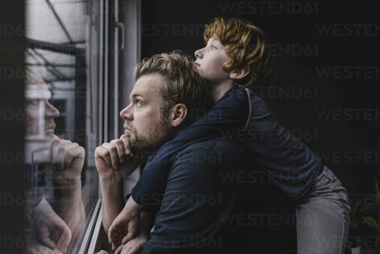 Father and son looking out of window on rainy day - KNSF06297 - Kniel Synnatzschke/Westend61