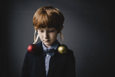 Portrait of redheaded boy wearing bow tie and Christmas baubles - KNSF06303
