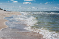 High angle view of sea waves rushing at beach against sky, Poland - MJF02412