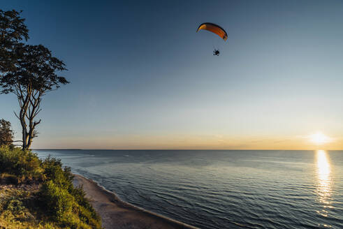 Paragliding over sea in Poland against clear sky - MJF02421