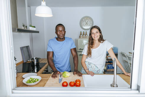 Portrait of couple preparing salad in kitchen - KIJF02645
