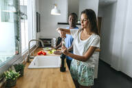 Woman opening bottle of wine next to man in kitchen - KIJF02648