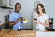 Couple eating salad and drinking wine in the kitchen - KIJF02651