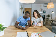 Happy couple using their cell phones at home - KIJF02657