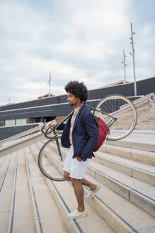Stylish man carrying bicycle on stairs in the city - AFVF03844