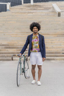 Portrait of stylish man with bicycle standing at stairs - AFVF03847