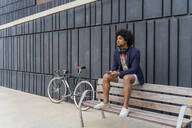 Stylish man with cell phone sitting on a bench - AFVF03856