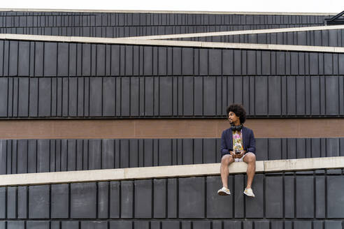 Stylish man with cell phone sitting on a wall - AFVF03862