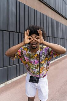 Portrait of man with a camera wearing colorful shirt - AFVF03871