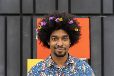 Portrait of man with blossoms in his hair wearing colorful shirt - AFVF03880