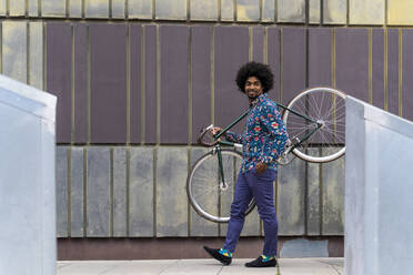 Stylish man carrying bicycle in the city - AFVF03886