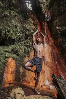 Man practising yoga at waterfall, tree position - LJF00715
