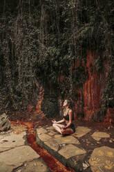 Young woman meditating at a waterfall - LJF00727