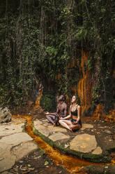 Couple meditating at a waterfall - LJF00730