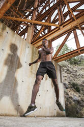 Young man jumping under a bridge - LJF00736