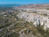 Aerial view of volcanic landscape against blue sky during sunny day at Cappadocia, Turkey - KNTF03070