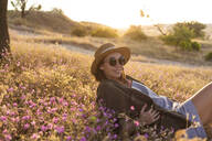 Young woman lying on meadow at sunset - KNTF03079