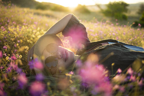 Young woman with sunhat lying on meadow at sunset - KNTF03082