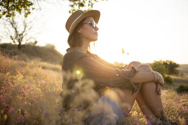 Young woman wearing sunhat, sitting on meadow at sunset - KNTF03085