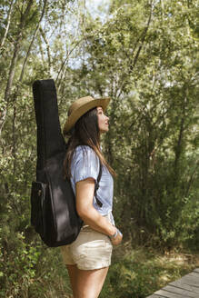 Young woman with guitar case looking up - LJF00744