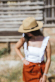Portrait of blurred young girl wearing straw hat - LJF00753