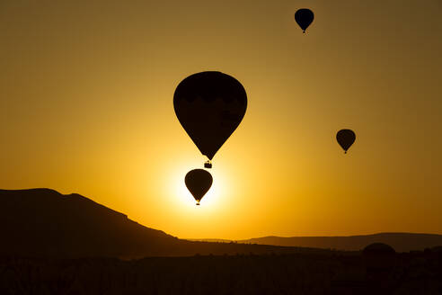 Silhouette hot air balloons flying over landscape against clear sky in Goreme during sunset, Cappadocia, Turkey - KNTF03092