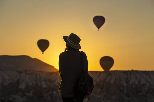 Rear view of silhouette young woman looking at hot air balloons while standing on land at Goreme, Cappadocia, Turkey - KNTF03095