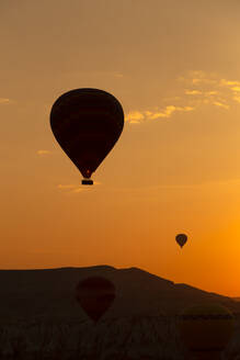 Silhouette hot air balloons flying over landscape in Cappadocia against sky at sunset, Turkey - KNTF03098