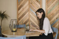 Young businesswoman using laptop and cell phone at table in a cafe - ALBF00967
