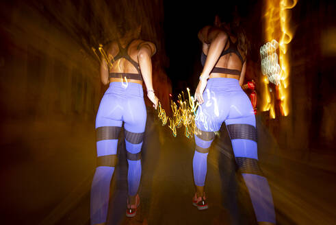 Long exposure photo of two women running in the city at night - OCMF00585