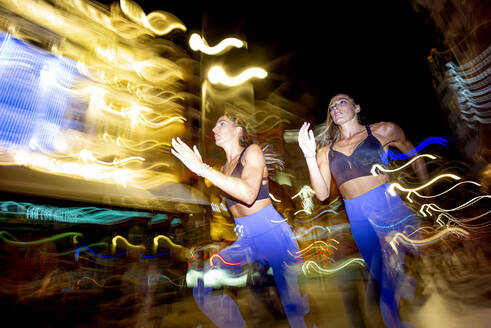Long exposure photo of two women running in the city at night - OCMF00588