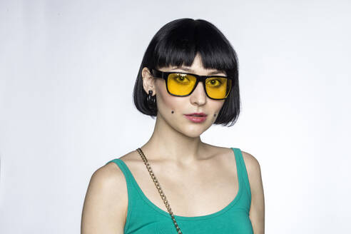 Portrait of young woman with cheek piercings and yellow glasses - VGF00295