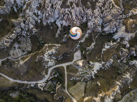 Aerial view of hot air balloon flying over rock formations at Goreme National Park, Cappadocia, Turkey - KNTF03136