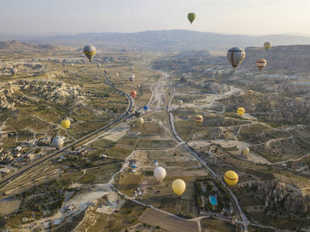 Aerial view of colorful hot air balloons flying over land at Goreme National Park, Cappadocia, Turkey - KNTF03145