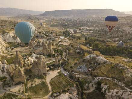 Aerial view of colorful hot air balloons flying over land at Goreme National Park, Cappadocia, Turkey - KNTF03148