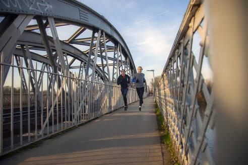 Two teenagers running over railway bridge - AJOF00004