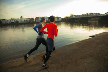 Two young men jogging along River Thames, London, UK - AJOF00007