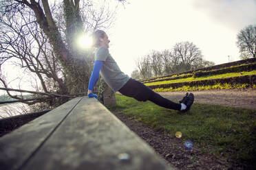 Young man doing press-ups on a wooden bench - AJOF00019