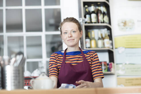 Portrait of woman with apron in a cafe - SGF02414