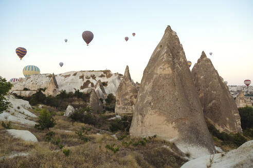 Hot air balloons flying over rocky landscape against clear sky, Cappadocia, Turkey - KNTF03246