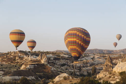 Colorful hot air balloons flying over landscape against clear sky at Cappadocia, Turkey - KNTF03249