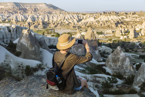 Rear view of young woman photographing landscape with smart phone at Goreme, Cappadocia, Turkey - KNTF03270